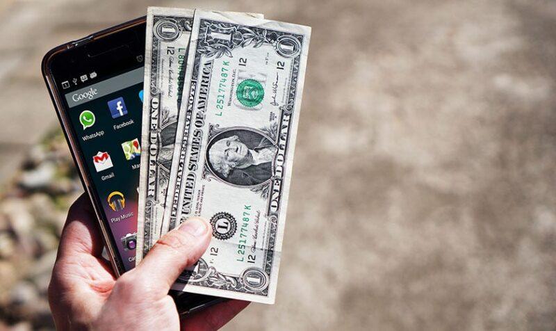 Najtańszy abonament - Dłoń trzymająca pieniądze i telefon